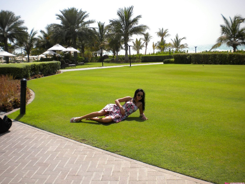 Туристка принимает солнечные ванны без одежды стоя под пальмой