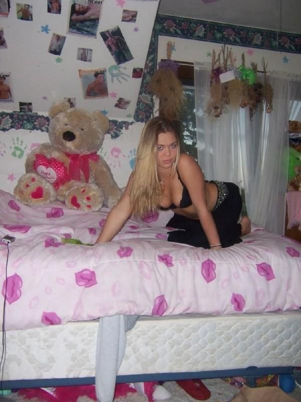 Горячая штучка показывает пирсинг в сиськах в своей спальне
