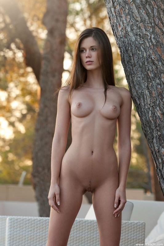 Голая милашка позирует около дерева