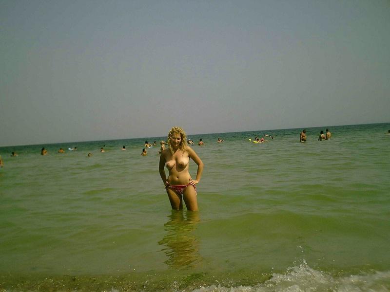Барышня позирует на пляже без нижнего белья
