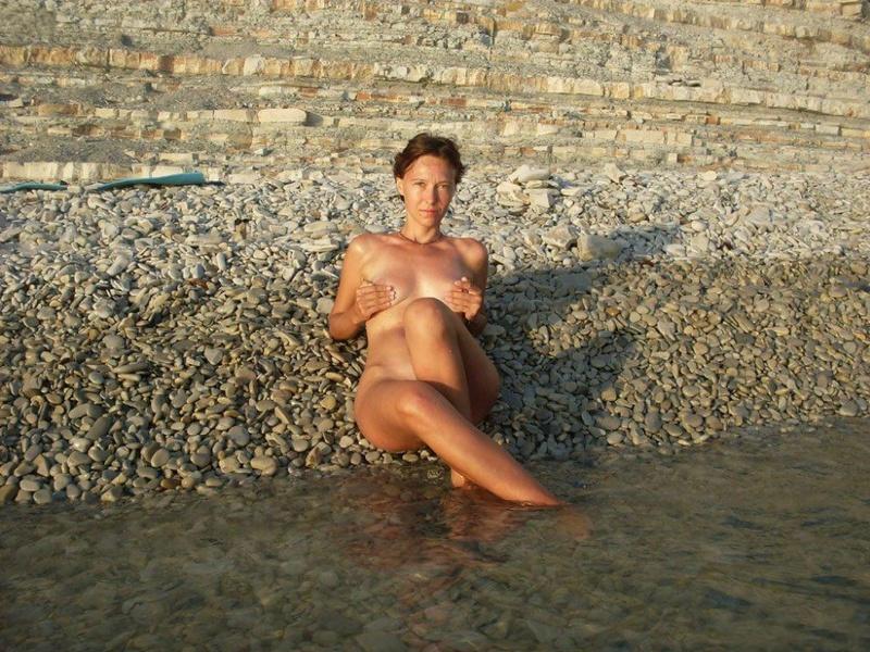 Нагая мамка отдыхает на галичном пляже