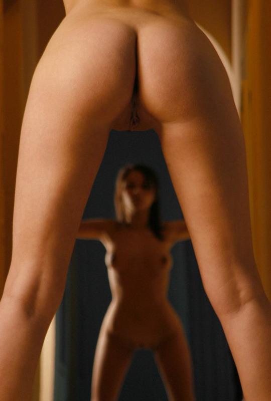 Обнаженная блядь о чем-то задумалась возле зеркала