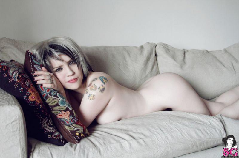 Татуированная грешница хвастается нагим телом в просторной комнате