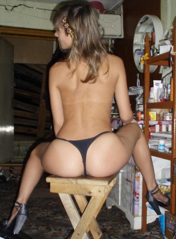 В сарае стройная студенточка спокойно сидит с голым торсом
