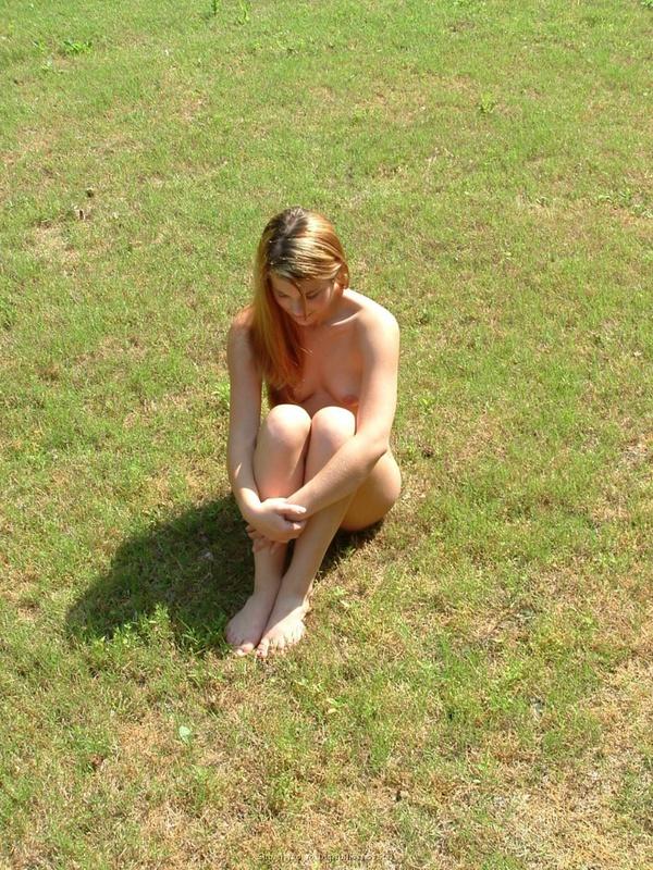 Голая девушка сидит на газоне
