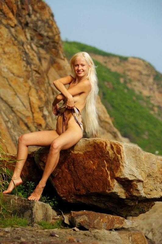 Похотливая блондинка спускает сарафан сидя на камне