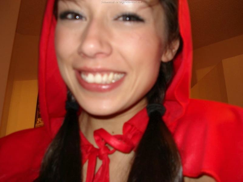 Брюнетка в квартире фотографируется в костюме красной шапочки