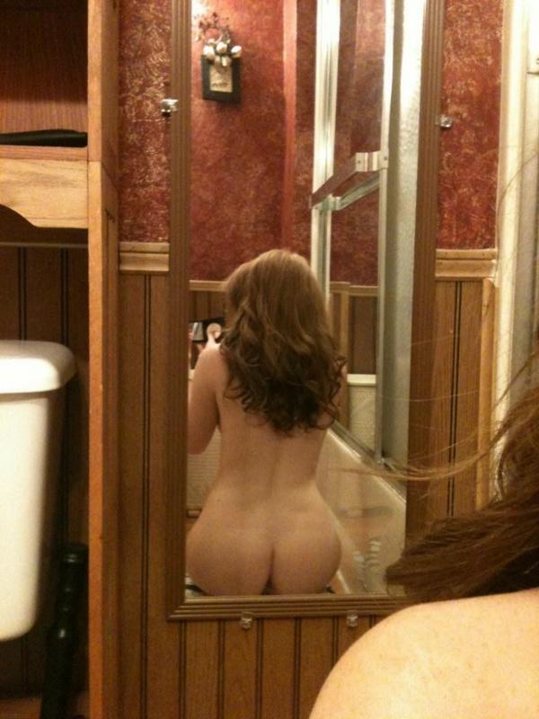 Молоденькая девушка снимается без нижнего белья перед зеркалом