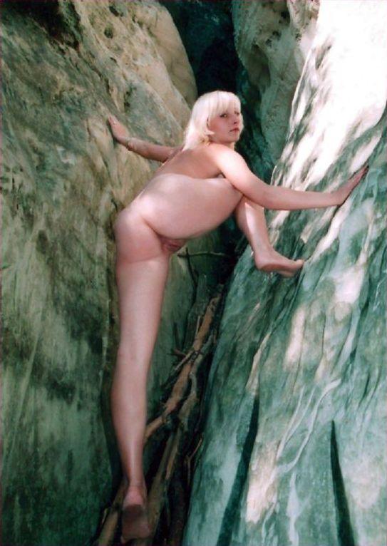 Голая блондинка позирует в пещере