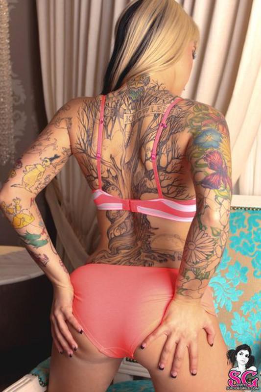 Татуированная нимфа оголила тело в комнате