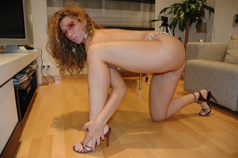 Обнаженная мамаша сидит на шкуре под столом