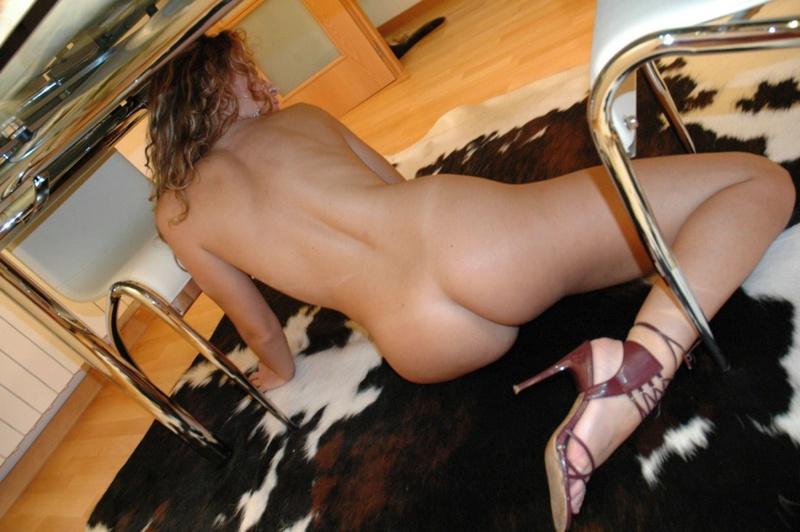 Голая мамка сидит на шкуре под столом