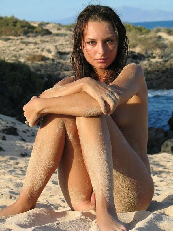 Смуглая сучка лежит на берегу моря