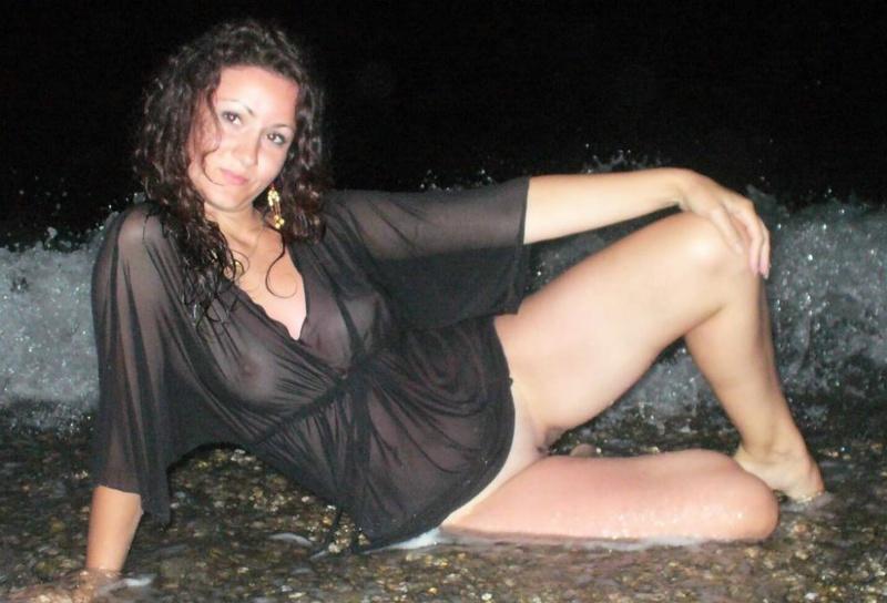 Шлюха в прозрачном платье лежит на песке