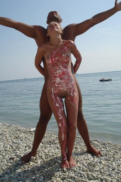Парень разукрасил туловище голой жены на песке