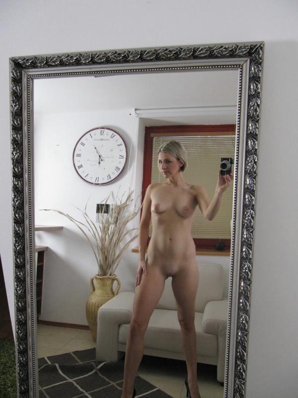 Игривая баба делает соблазнительные селфи стоя у зеркала