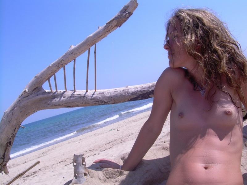 Кучерявая чувиха раздевается на песке
