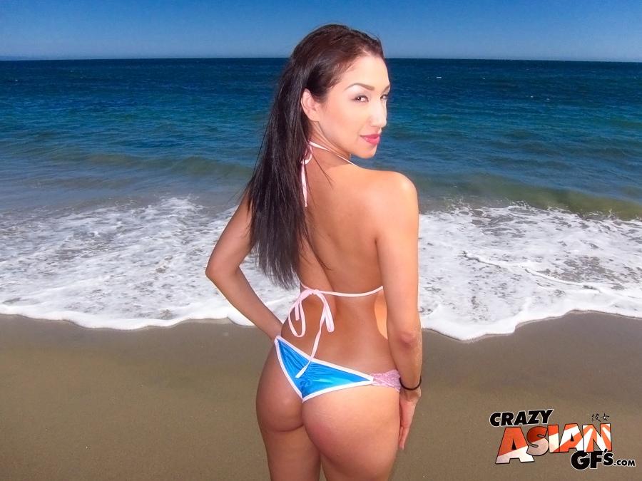 Худенькая азиаточка в бикини отдыхает на пляже