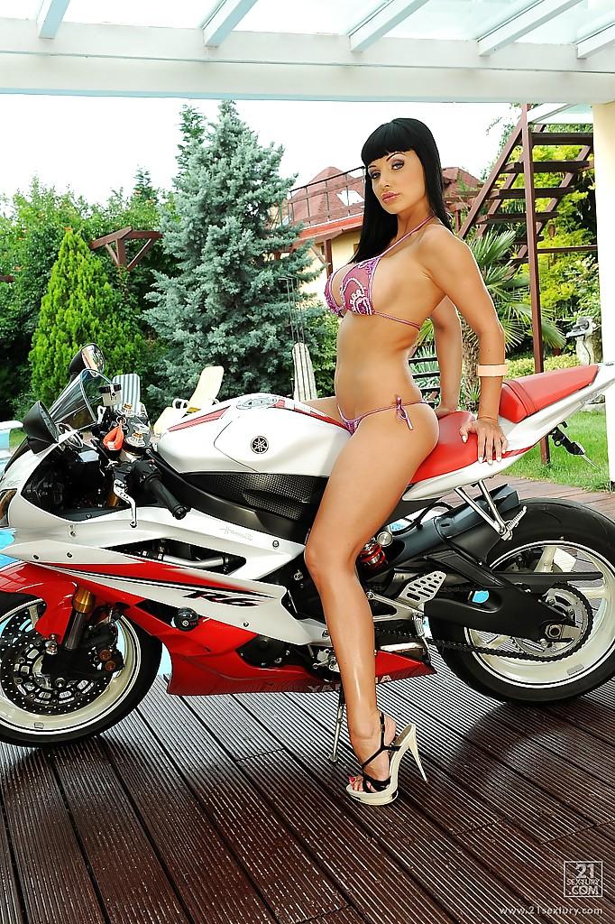 Наполовину раздетая брюнетка фоткается на фоне мотоцикла