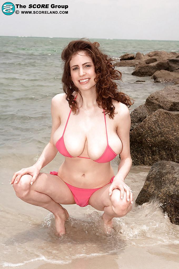 Сисястая бабёнка раздевается среди громадных валунов на диком пляже