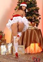 Сексуальная милашка Eve Angel в костюме Санты зажигает возле елки 4 фотография