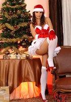 Сексуальная милашка Eve Angel в костюме Санты зажигает возле елки 7 фотография
