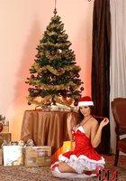 Сексуальная милашка Eve Angel в костюме Санты зажигает возле елки 11 фотография