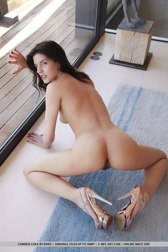 Молодая любовница позирует голышом у панорамной стены