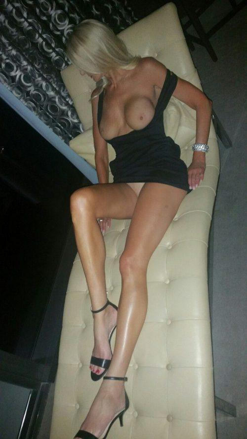 Светловолосая девушка на диване хвастается силиконовым бюстом