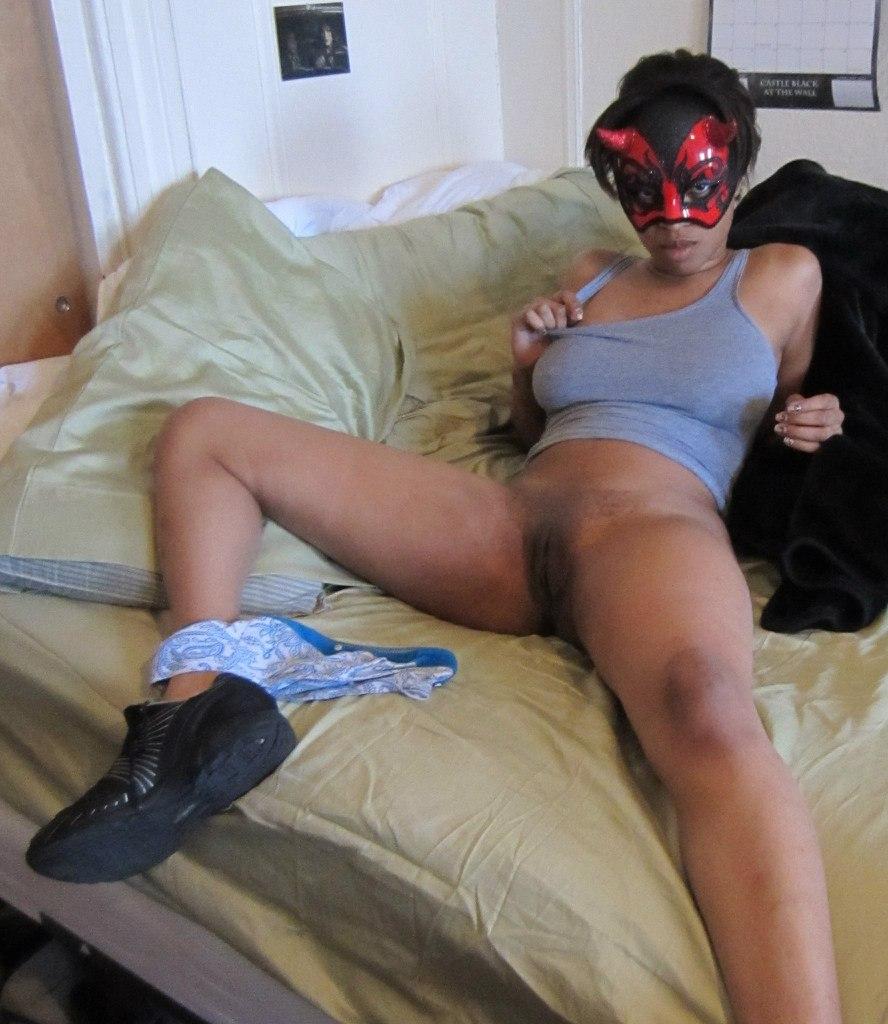 Негритянка в маске на койке обнажает узкую вагину