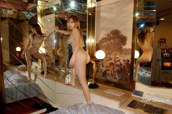 Рыжая азиатка позирует на постели после ванны