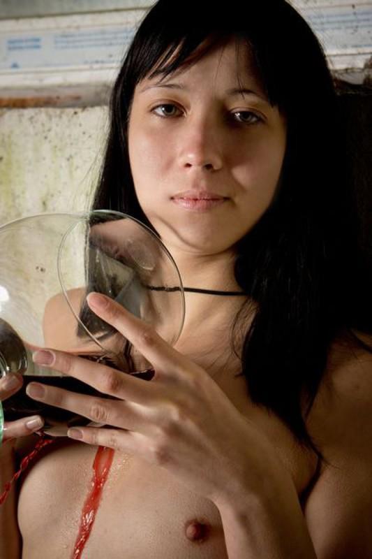 Модель с темными волосами поливает вином полуголое тело в заброшке