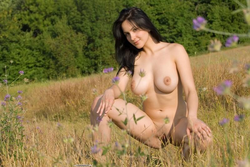Роскошная шатенка без одежды делает селфи в поле