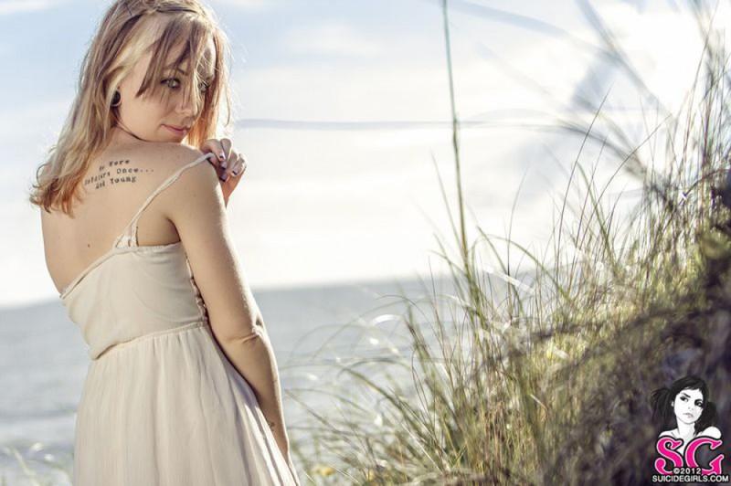 Красивая дева хвастается собой в траве на берегу моря