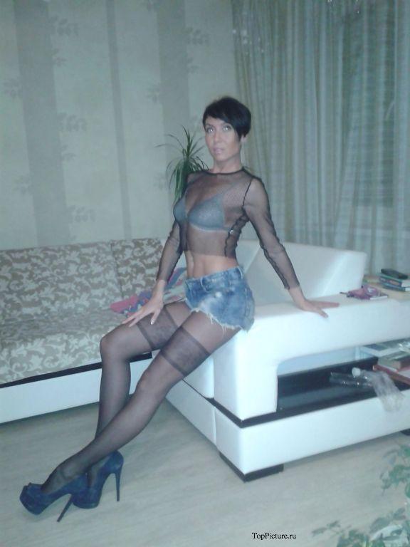 Брюнетистая мамка развратно позирует на диване в колготах