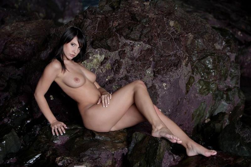 Раздетая брюнетка бахвалится грудями в пещере