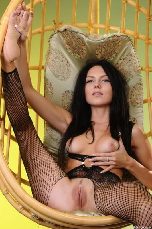 Темноволосая девка демонстрирует вагину сидя в необычном кресле