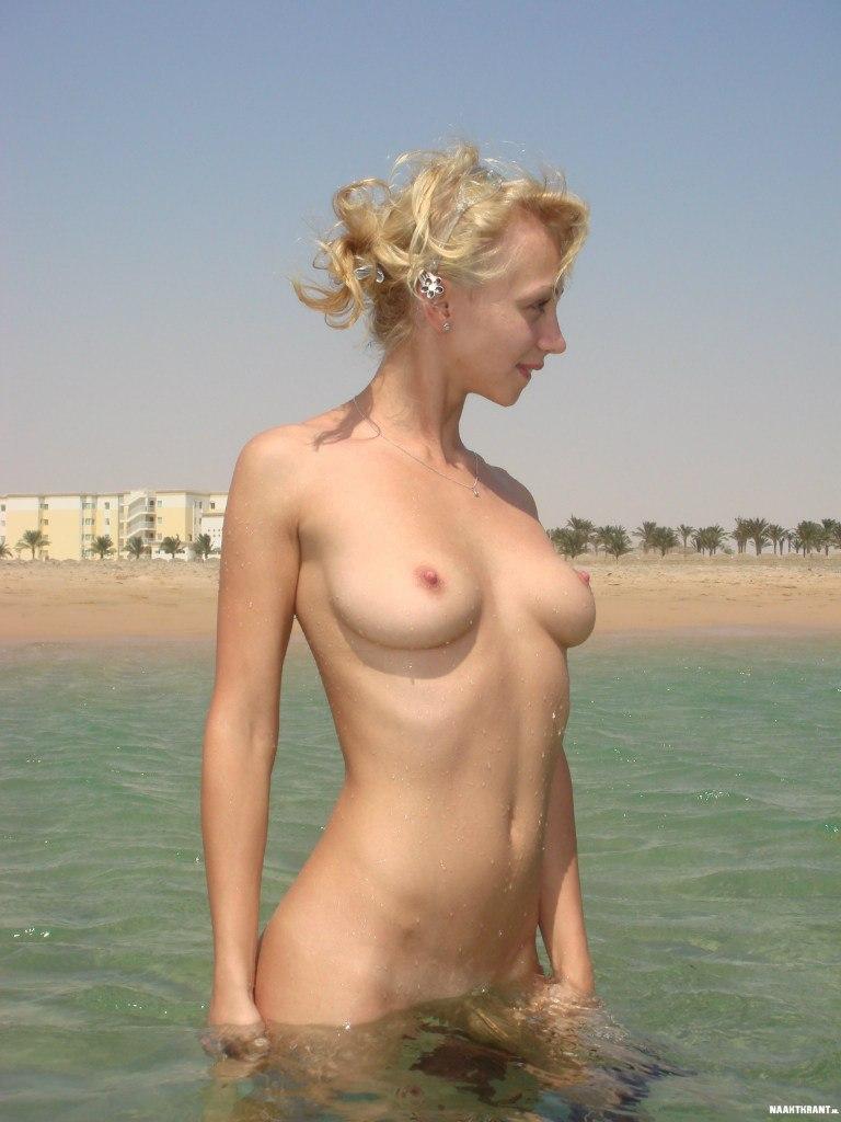 Нежная блондинка показывает голое тело на море