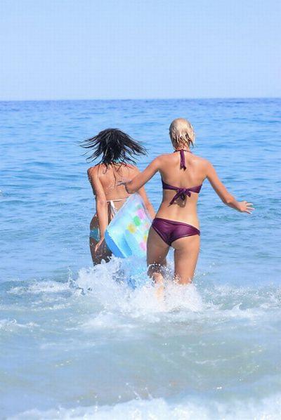 Девушки в купальниках бегают по пляжу