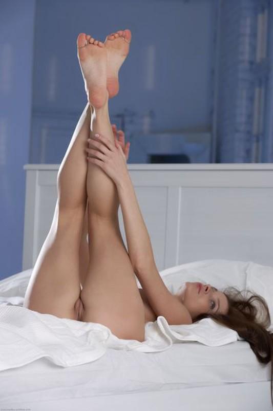 Нежная милашка позирует на белоснежной постели