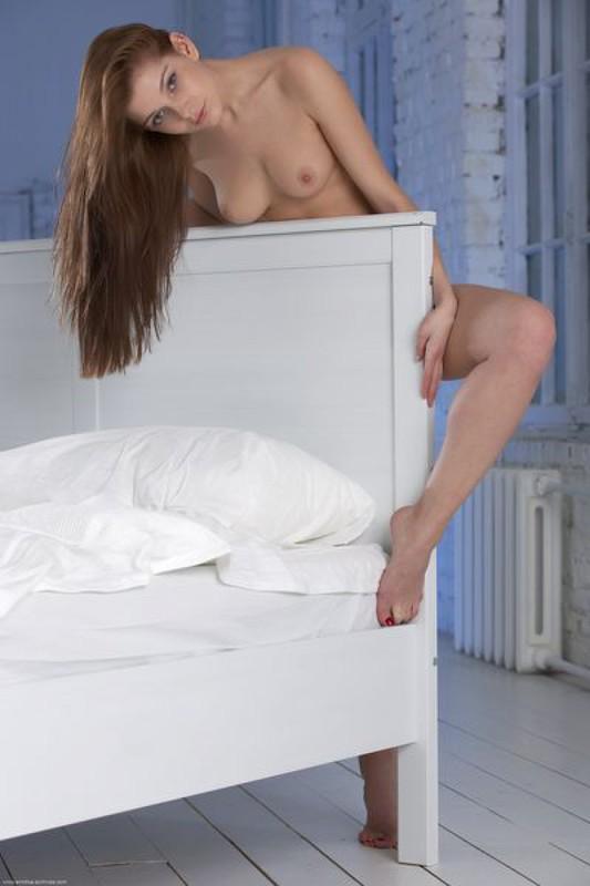 Сексуальная красавица бахвалится на светлой кровати