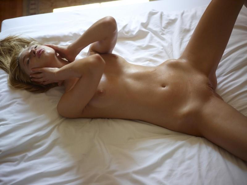 Восхитительная красоточка показывает гладкую пилотку лежа на спине