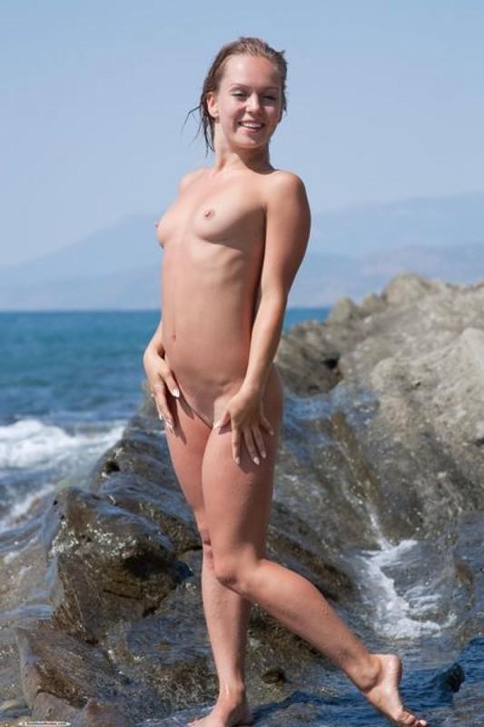 Голая девушка позирует на скалистом берегу моря