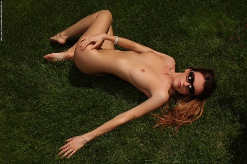 На заднем дворе телка поливает голые груди из лейки