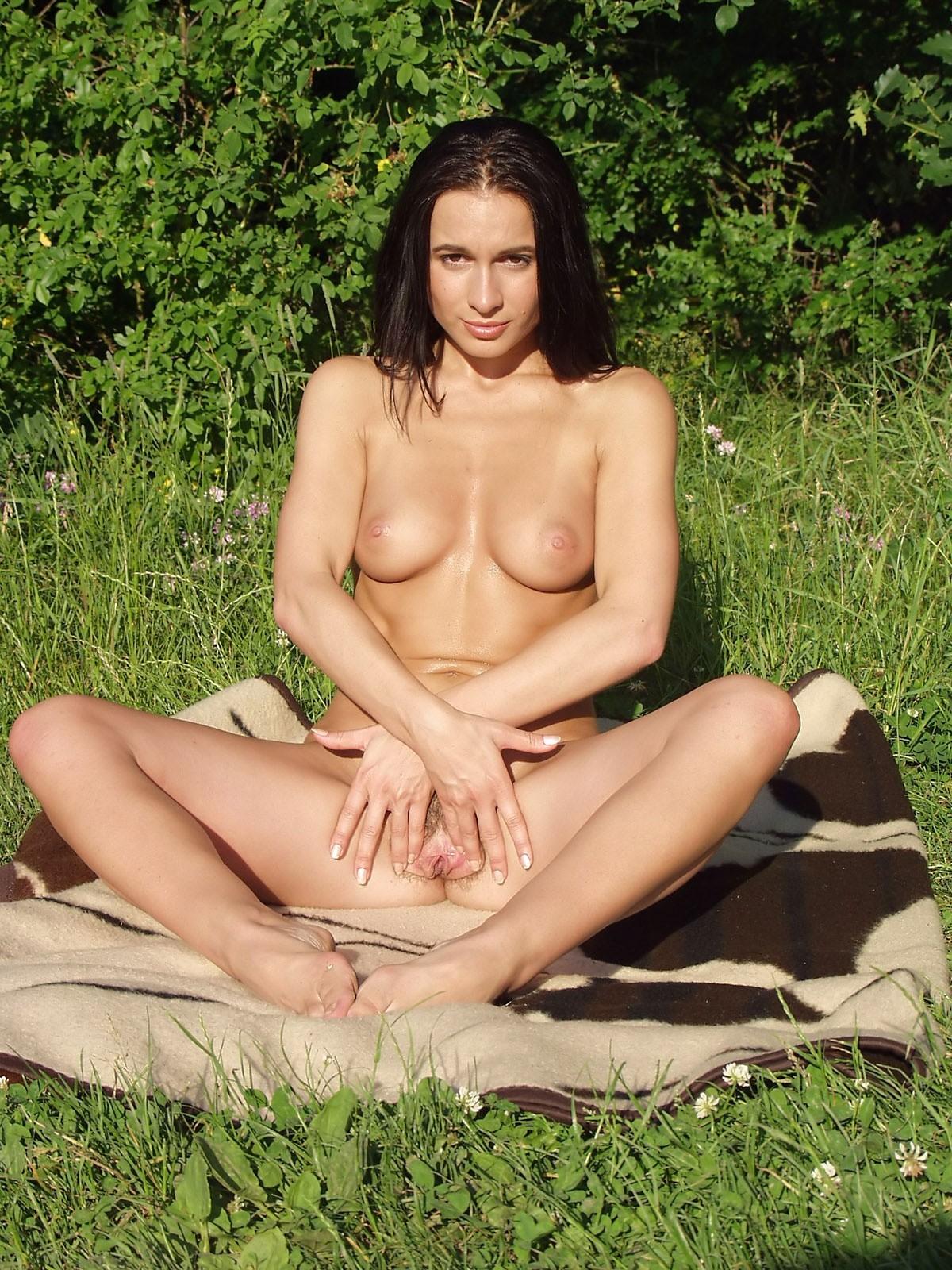 На зеленой полянке темноволосая девка блистает волосатой вульвой секс фото