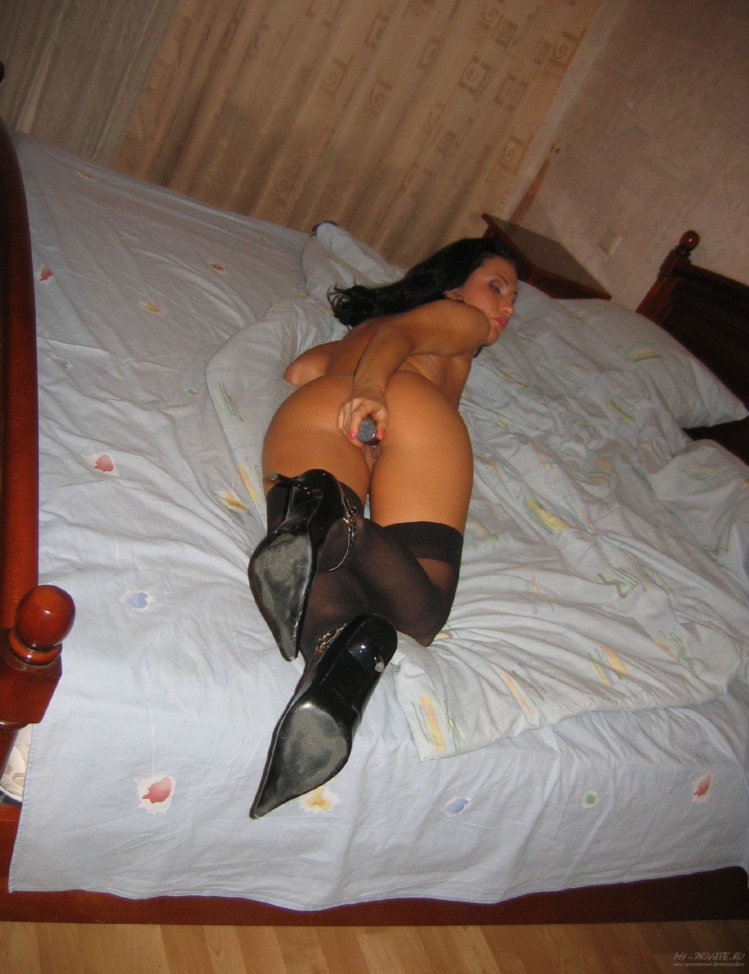 Темненькая девушка трахает свою писюшку в кроватке