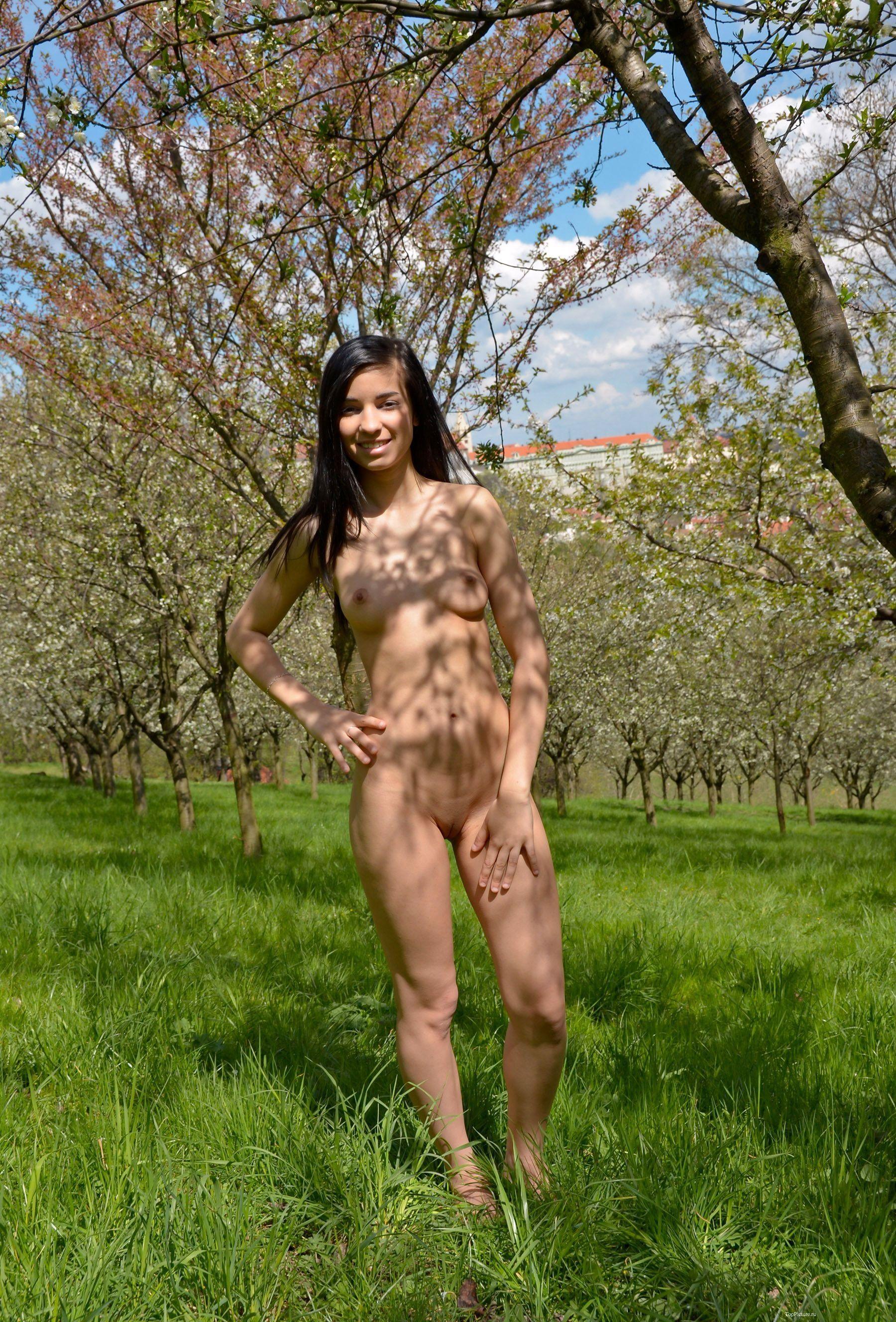 Брюнетка голышом позирует в саду где ходят люди