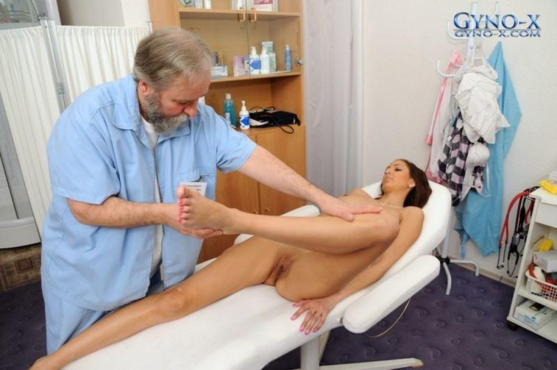 На рабочем месте старый врач заводит за грудь раздетую пациентку