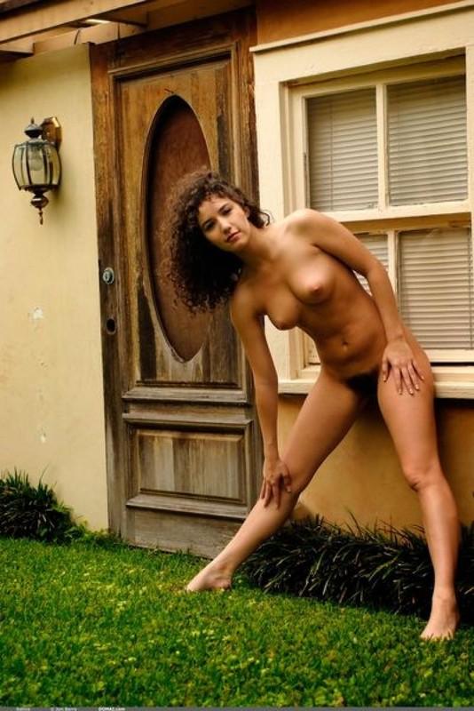 Кудрявая милашка нагишом позирует на заднем дворе