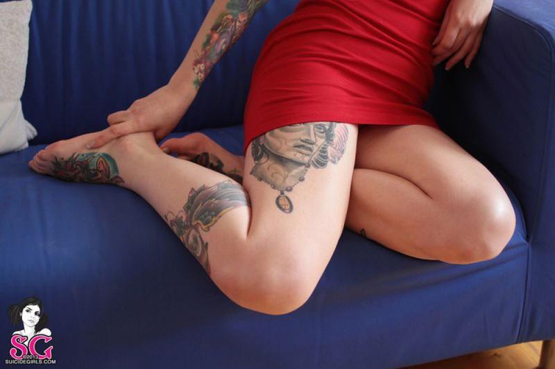 Татуированная бестия лежит на полу голышом